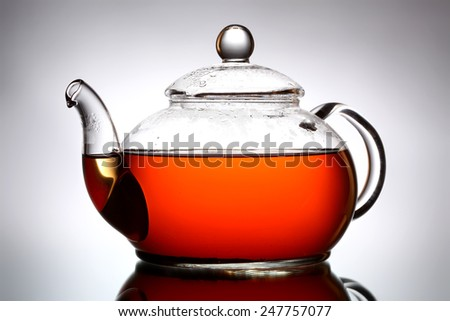 Glass teapot on gray background - stock photo