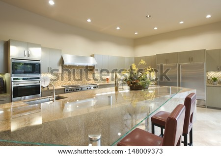 Glass topped breakfast table in modern kitchen - stock photo