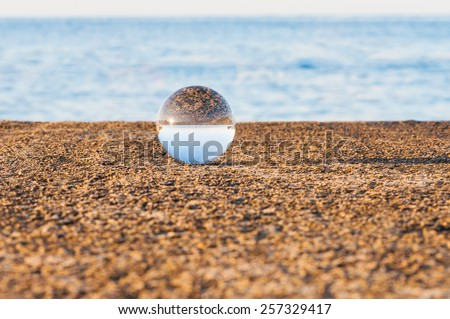 Glass transparent ball on blue water background and grainy surface. Texture, outdoors - stock photo