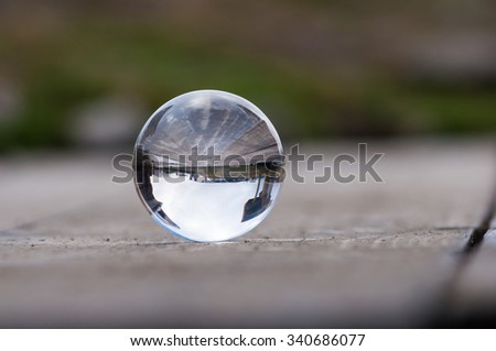 Glass transparent ball on dark green background and wooden surface. Soft focus. With empty space for text - stock photo