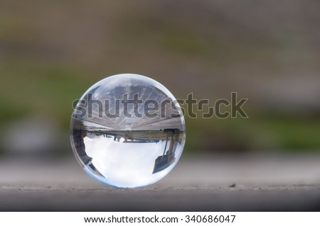 Glass transparent crystal ball on dark green background and wooden surface. Soft focus. With empty space for text - stock photo