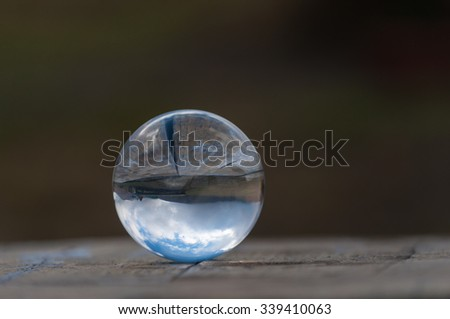 Glass transparent crystal glass ball on dark green background and wooden surface. Soft focus. With empty space for text. - stock photo