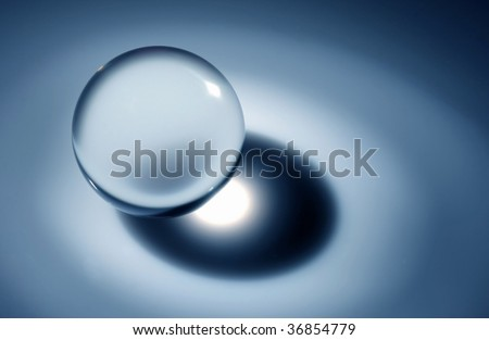 Glass transparent sphere in a ray of light - stock photo