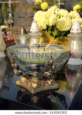 Glass votive candle lit on black marble tombstone - stock photo