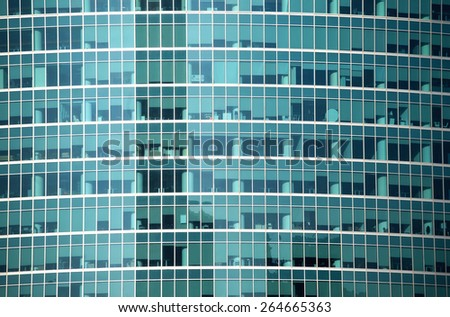 Glass wall of modern office building with many large panoramic windows in business cluster front view close-up - stock photo