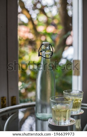 glass water bottle  on natural background - stock photo