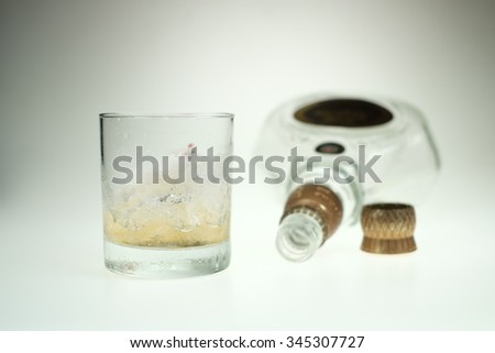 Glass, whiskey and empty bottles on the bar. Abuse of alcohol hangover. Alcoholism concept. Drunk driver concept - stock photo