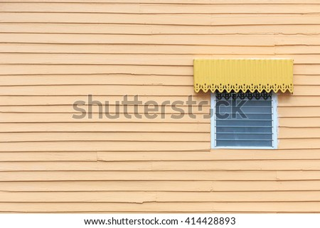 Glass window on orange wooden wall exterior - stock photo