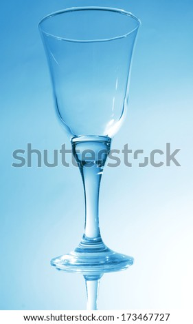 glass wine on blue mirror background - stock photo