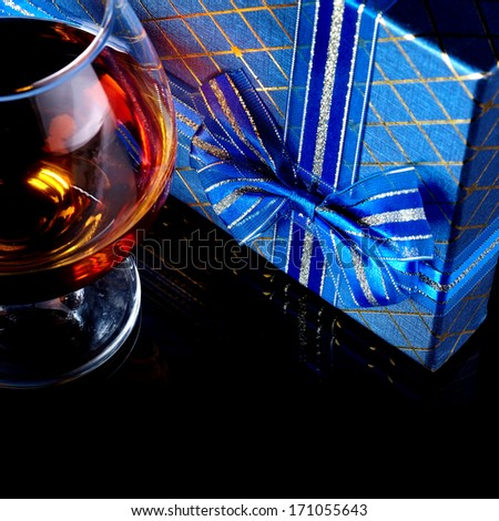 Glass with alcohol and a gift. Alcohol and gift box. Box with a bow and glass with drink. - stock photo