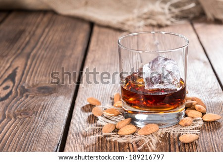 Glass with Amaretto and ice cubes on dark background with some almonds - stock photo