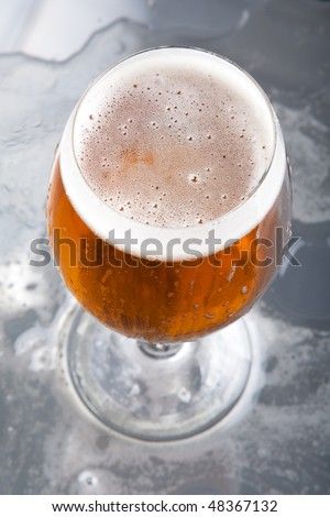 Glass with beer and foam - stock photo