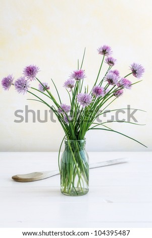 Glass with blooming chive. - stock photo