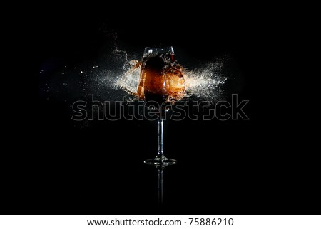 Glass with brown liquid exploded by bullet with many splashes around at the black background - stock photo