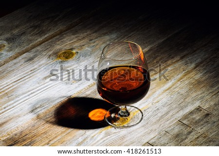 glass with cognac on a wooden background - stock photo
