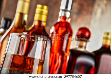 Glass with drink and bottles of assorted alcoholic beverages. - stock photo