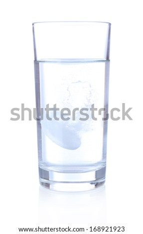 Glass with efervescent tablet in water with bubbles isolated on white - stock photo