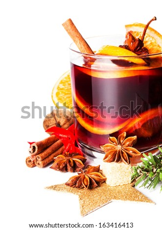 Glass with Hot red mulled wine for winter and Christmas with orange slice, anise and cinnamon sticks isolated on white background, macro - stock photo