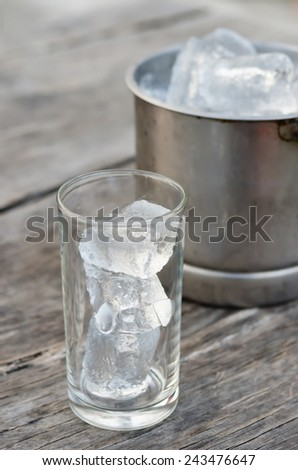 Glass with ice cubes and Ice bucket filled with ice cubes - stock photo