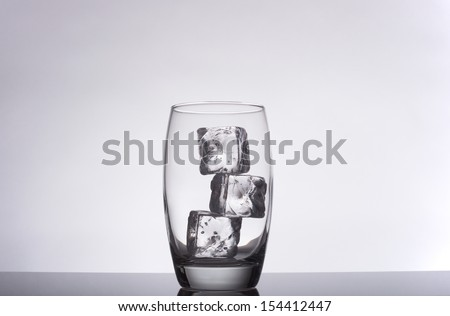 glass with ice cubes on a gradient background - stock photo
