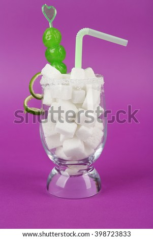 Glass with lump sugar, cocktail straw, cherries on purple background - stock photo