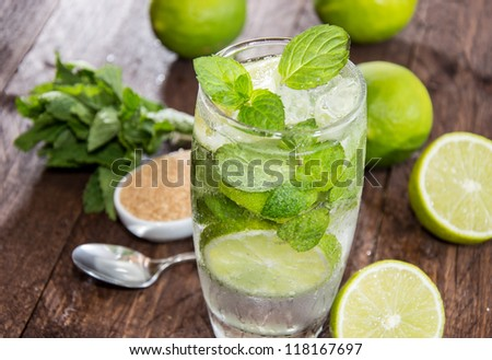 Glass with Mojito and crushed ice on wooden background - stock photo