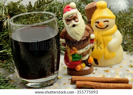 Glass with red wine and chocolate Santa Claus on table - stock photo