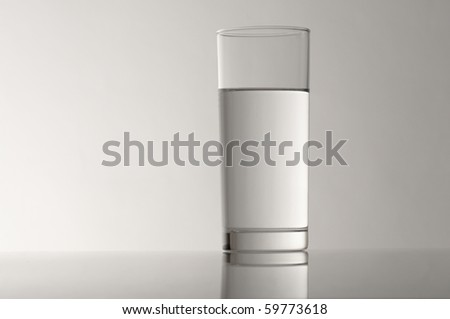 glass with spring water against a grey background - stock photo