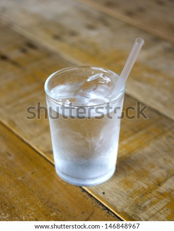 Glass with water on wood background - stock photo