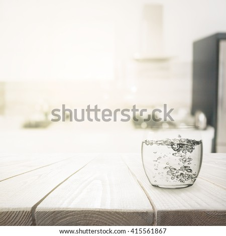 Glass with water on wooden table over blured kitchen interior background - stock photo