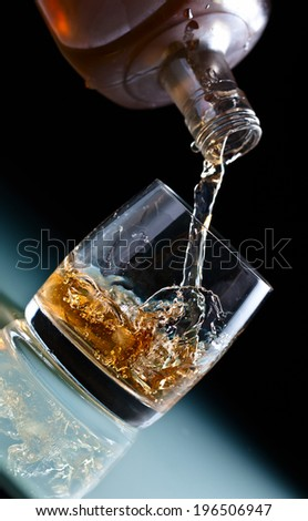 glass with whiskey and ice on a glass table  - stock photo