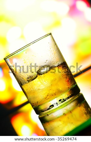 Glass with whiskey closeup over colorful background - stock photo