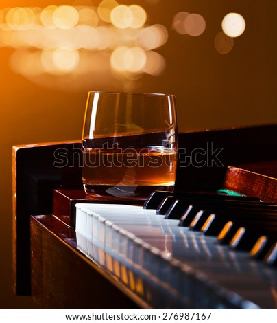 glass with whiskey on a old piano - stock photo