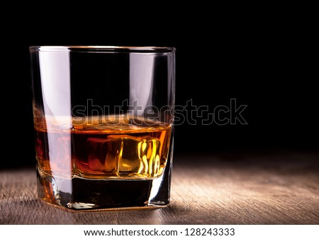 glass with whiskey on wooden table - stock photo