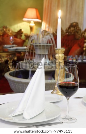 glass with wine, white napkin and candle at table, fountain in restaurant - stock photo