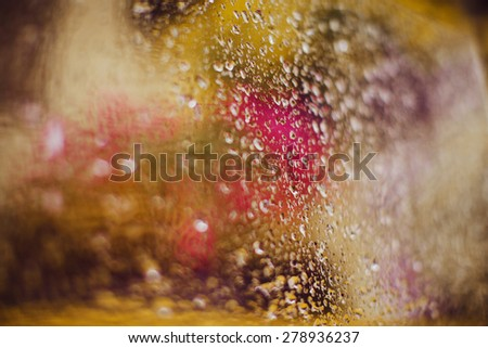 glass with yellow and purple blurs and raindrops, background - stock photo