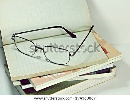glasses and book in retro style - stock photo