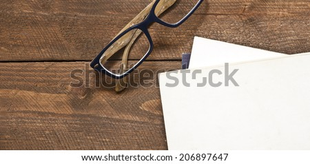 Glasses and book on wood. Warm natural light. Panoramic - stock photo