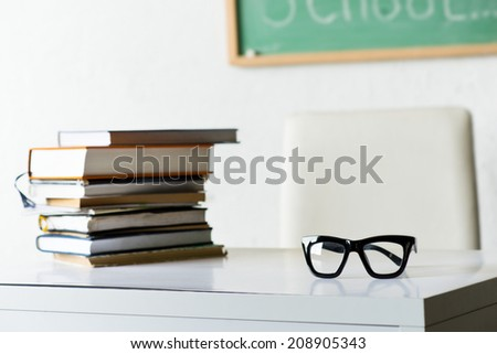 Glasses and books on the table in the classroom - stock photo
