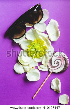 glasses and lollipop on white rose petals, vintage color preset - stock photo