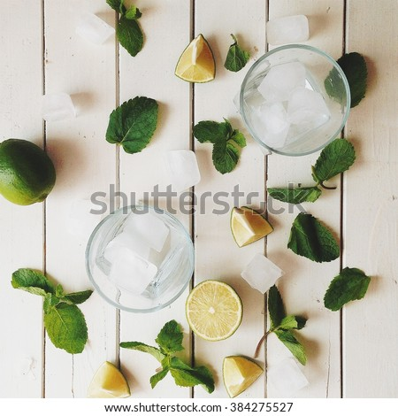 Glasses and mojito made with lime, ice and mint at white background. Flat lay, top view - stock photo