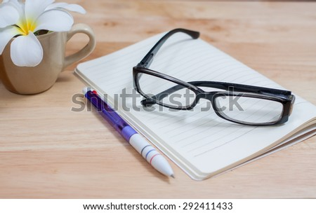 Glasses and pen on a notebook. - stock photo