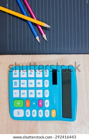 Glasses and pen on a notebook,Calculator - stock photo