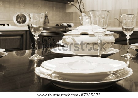 glasses and plates on a wooden table - stock photo