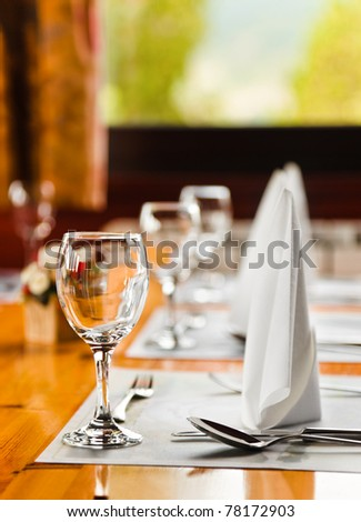 Glasses and plates on table in restaurant - food background - stock photo