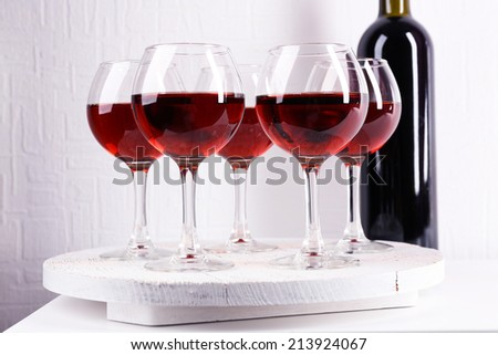Glasses and wine bottle on tray in room - stock photo