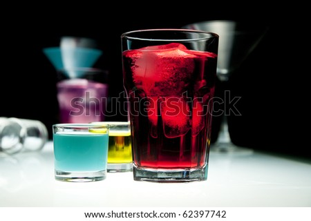 Glasses filled with colored alcohol, black background. - stock photo