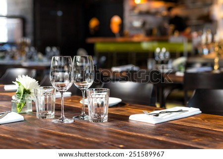 Glasses, flowers, forks, knives served for dinner in restaurant with cozy interior. - stock photo