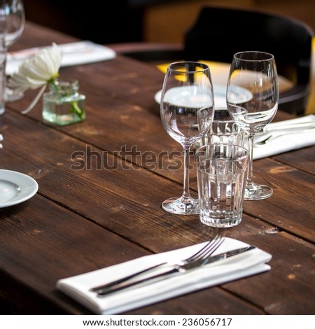 Glasses, forks, knives, napkins and decorative flower on a dark old brown wooden table served for dinner in cozy restaurant - stock photo