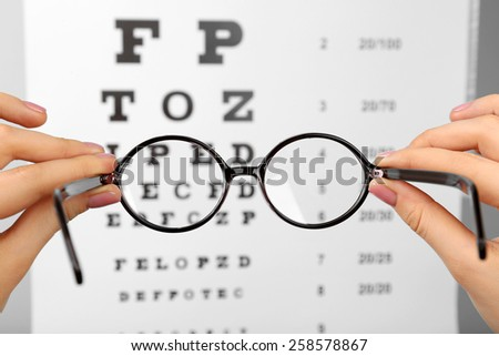 Glasses in hands on eye chart background, close-up - stock photo